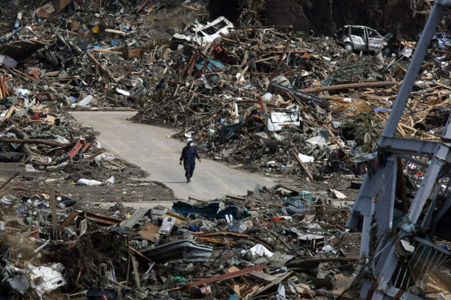A man walks through tsunami debris stacked along a street in Japan on Thursday. Japan's government estimated the damage from the tragedy at as much as $309 billion. Photo: Tomohiro Ohsumi, Bloomberg