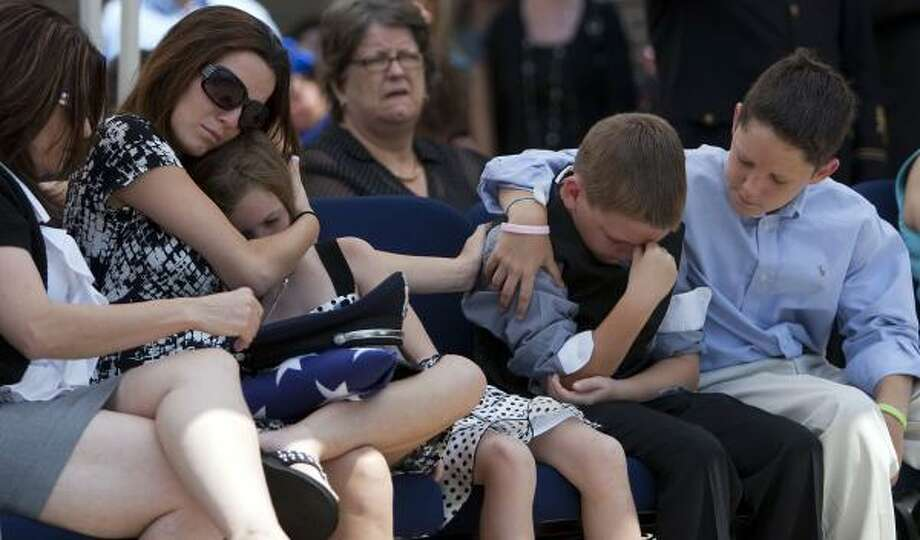 Alisha Will, who is six months pregnant, comforts her daughter, Abby, as her son Alex is consoled by friend Tanner Lee at the funeral of HPD officer Kevin Will, 37. Photo: Johnny Hanson, Chronicle