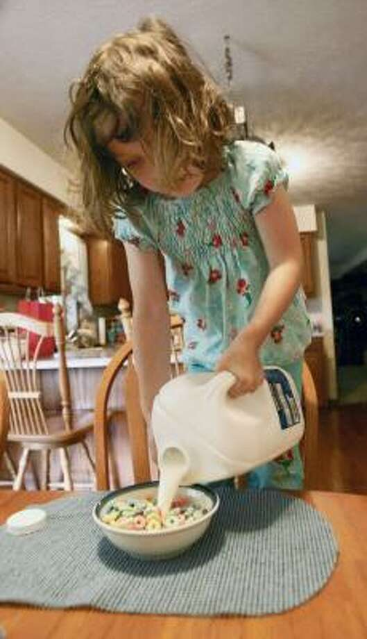 Taylor Yost pours milk onto her cereal in Zelienople, Pa. Food costs fell 0.2 percent in April. The price of dairy products dropped sharply. Photo: Keith Srakocic, Associated Press