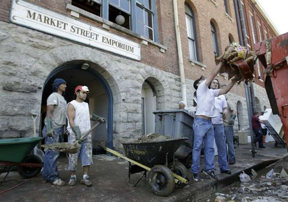Workers clean up the lower level of the Music City Emporium, one of the businesses damaged in downtown Nashville, Tenn. Photo: MARK HUMPHREY, ASSOCIATED PRESS