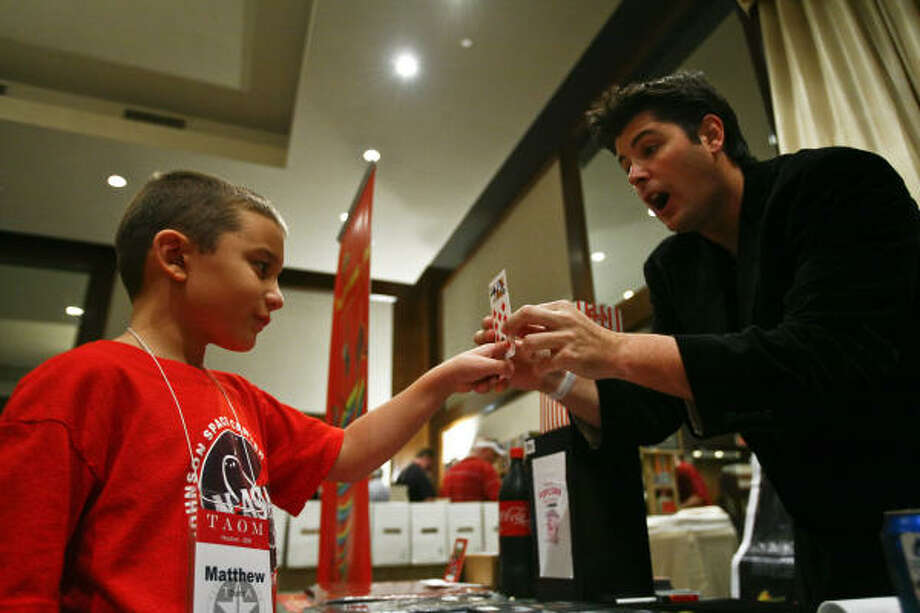 George Iglesias performs a magic trick for 7-year-old Matthew Dunn at the Texas Association of Magicians convention at the Omni Riverway Resort on Saturday. Photo: Michael Paulsen, Chronicle