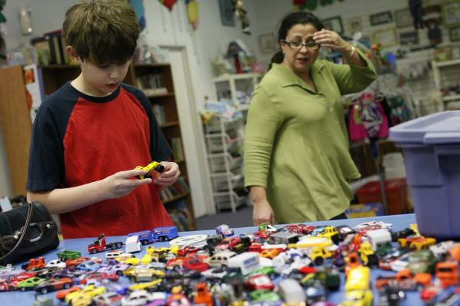 Debi Pfitzenmaier, with her son, Aaron, 12, drops off toys that her kids no longer play with at Kids Junction Resale in San Antonio. Photo: LISA KRANTZ, SAN ANTONIO EXPRESS-NEWS