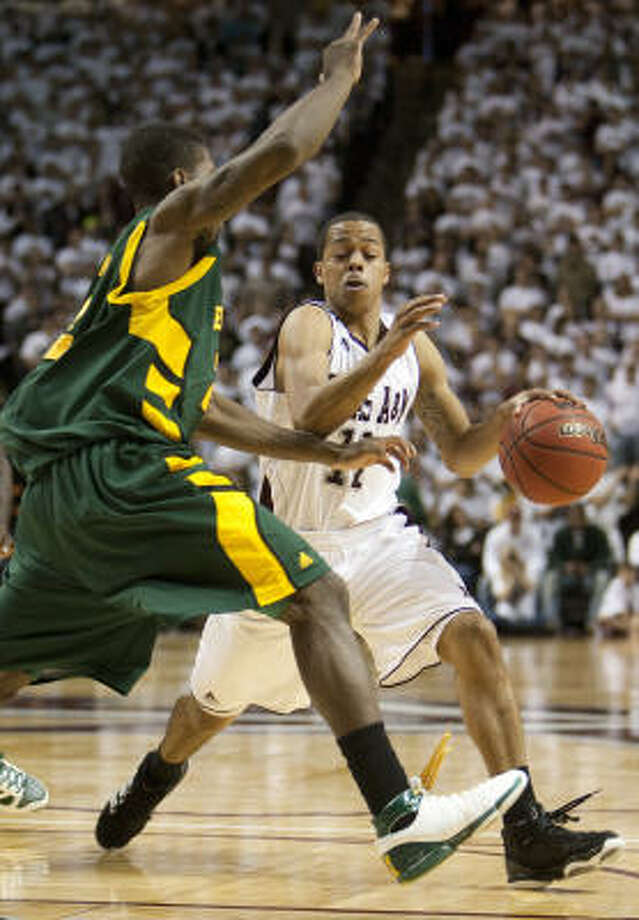 Texas A&M's B.J. Holmes drives against Baylor's A.J. Walton. Photo: Jon Eilts, AP