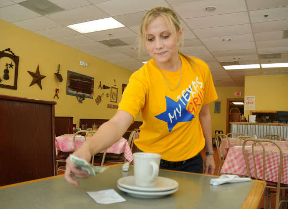 waitress Amber Taylor, a waitress at Texas Grill, 604 N. Loop 336 West, cleans a table and picks up her two-dollar tip from four diners who had a $23 bill. Photo: David Hopper, For The Chronicle