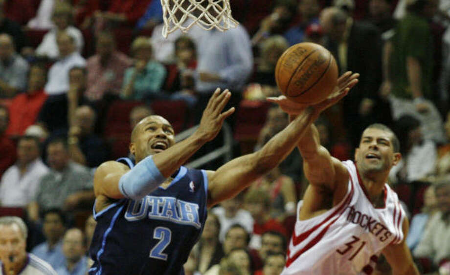 Houston's Shane Battier, right, blocks a shot by Utah's Derek Fisher. Photo: James Nielsen, Chronicle