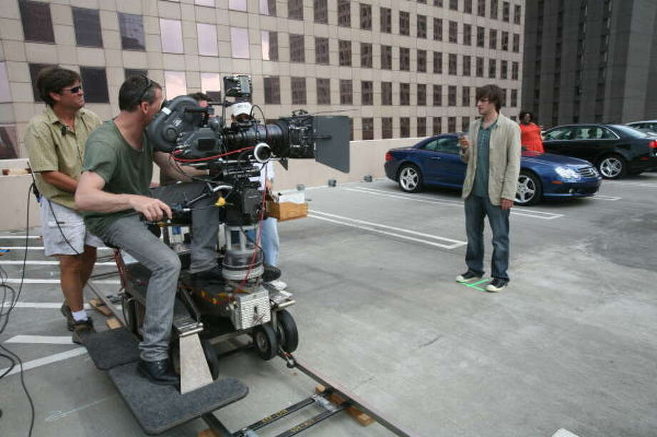Director of Photography Peter Vermeer, at camera, and dolly grip Sean Maxwell, far left, rehearse with actor Patrick Moote during the filming of a commercial for a German cell phone company. Photo: Steve Campbell, Houston Chronicle