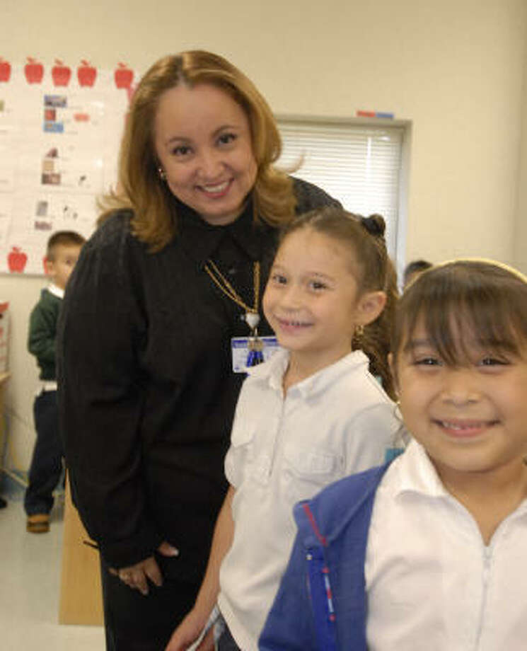 Elda Guadalupe Pacheco, Aldine ISD's bilingual teacher of the year, comes from a long line of educators in Yucatan, Mexico. She teaches bilingual pre-kindergartners, including five-year-olds Carolina Real, left, and Evelyn Perales. Photo: Tony Bullard, Tony Bullard