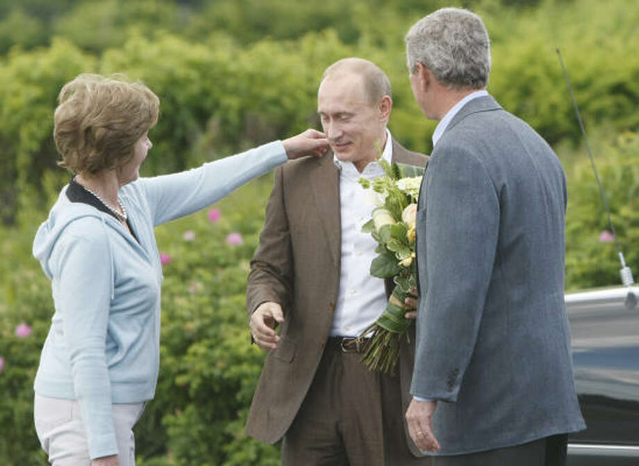 First Lady Laura Bush adjusts Russian President Vladimir Putin's collar as he arrives at Walker's Point Sunday in Kennebunkport, Maine, for a meeting with President George W. Bush, right. Photo: GERALD HERBERT, AP