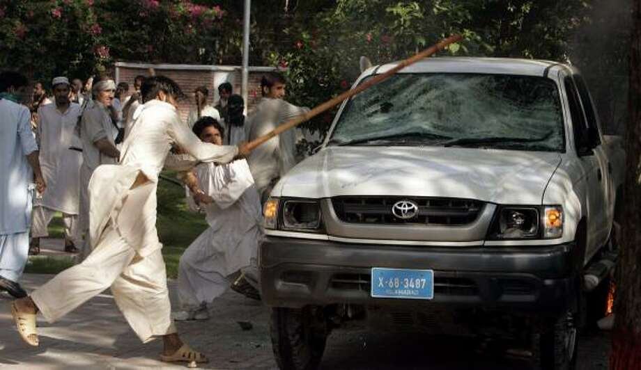 Angry religious students damage a vehicle after a clash outside the Lal Masjid, or Red Mosque, in Islamabad, Pakistan. The students and government officials each blamed the other for initiating Tuesday's violence. Photo: ANJUM NAVEED, ASSOCIATED PRESS