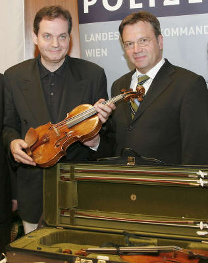 Interior Minister Guenther Platter, right, returned a  Stradivarius violin worth at least $2.7 million to its owner, Christian Altenburger, on Wednesday, more than a week after it was stolen from the musician's wall safe in Vienna. Photo: HANS PUNZ, AP