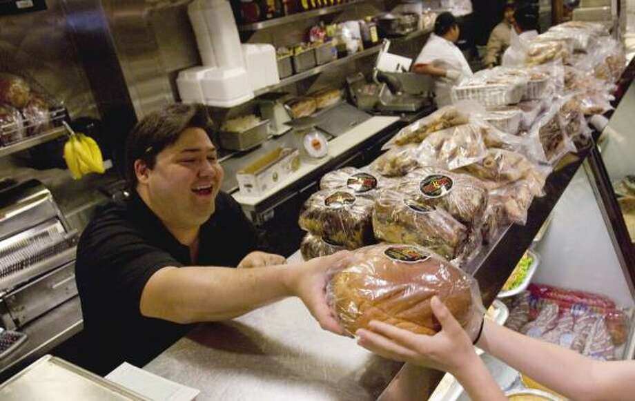 Ziggy Gruber of Kenny & Ziggy's Deli gives challah to a customer Sunday. Gruber says the store plans to bake four times as many loaves of challah this year to fill customers' needs, with Three Brothers closed for repairs. Challah is a traditional part of dinner for the Jewish New Year. Photo: BRETT COOMER, CHRONICLE