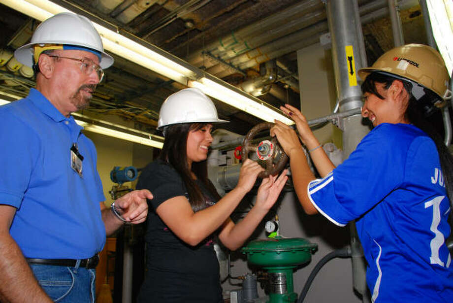 HANDS-ON TRAINING: Process technology professor Michael Speegle allows Sam Rayburn High School students Darlene Murrillo and Lizeth Deleon to demonstrate some of the daily duties of process technicians within the department?s process laboratory at San Jacinto College Central.