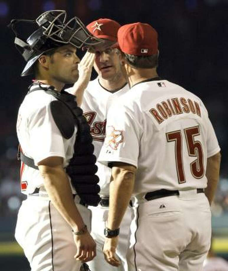 As catcher Ivan Rodriguez, left, listens, Astros starter Roy Oswalt, middle, receives encouragement from pitching coach Dewey Robinson during a rocky second inning. Photo: David J. Phillip, Associated Press