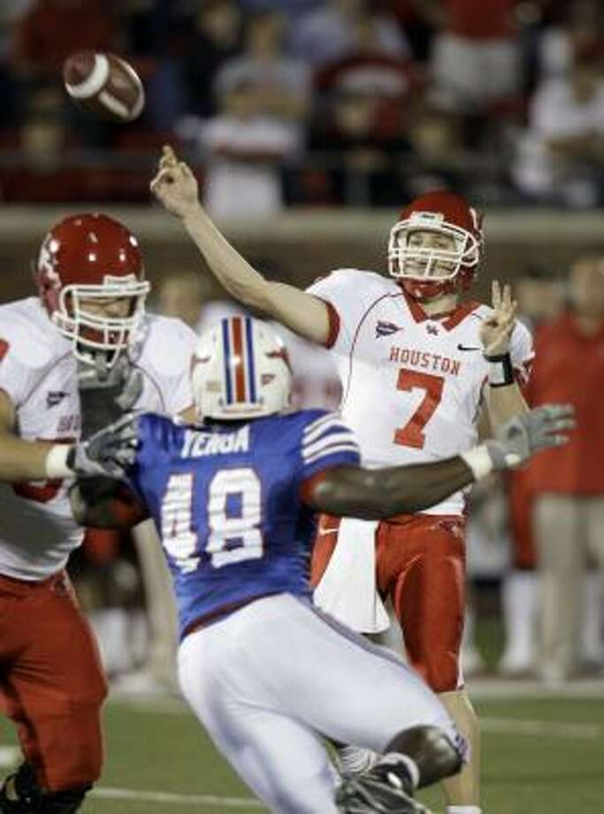 Case Keenum lets it fly as teammate Sebastian Vollmer, lert, dispatches SMU defender Youri Yenga during the first half. Photo: LM Otero, AP