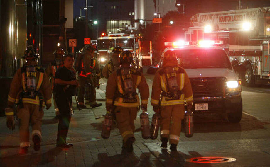 Firefighters battle a blaze on the 16th floor of a high-rise office building Tuesday evening at McKinney and Fannin in Houston. Photo: Melissa Phillip, Chronicle
