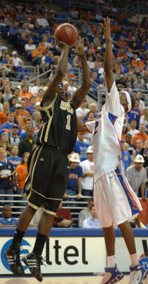 Central Florida's Jermaine Taylor, left, shoots for three points while being defended by Florida's Corey Brewer. Photo: PHIL SANDLIN, AP