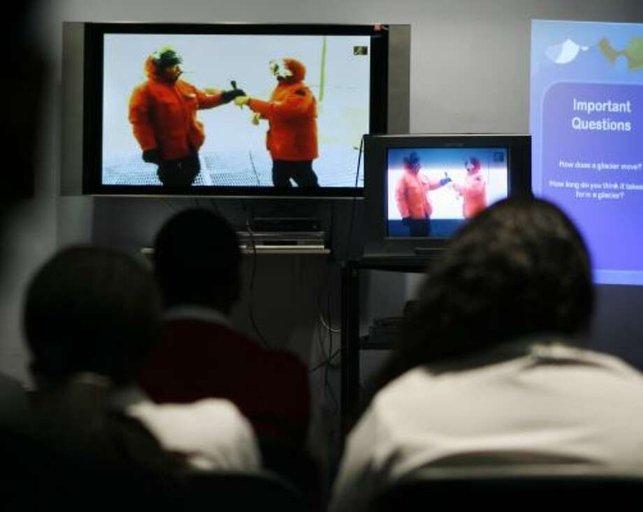 Students at the Promise Academy in Harlem listen to one of their teachers, Shakira Petit, at right on the television, talk to them from Antarctica via satellite on Tuesday. Photo: SETH WENIG, ASSOCIATED PRESS