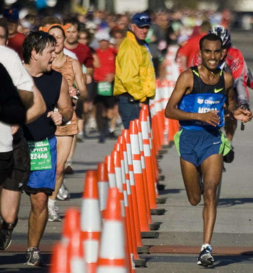 Stephen Lacy of Sugar Land shouts encouragement to Deriba Merga of Ethiopia as he nears the finish line to win the 2009 Chevron Houston Marathon. Because many half marathons run simultaneously with a marathon, half-marathon runners enjoy the same big-race accommodations. The 2010 Aramco Houston Half Marathon sold out 20 hours after registration opened in July. Photo: SMILEY N. POOL:, CHRONICLE