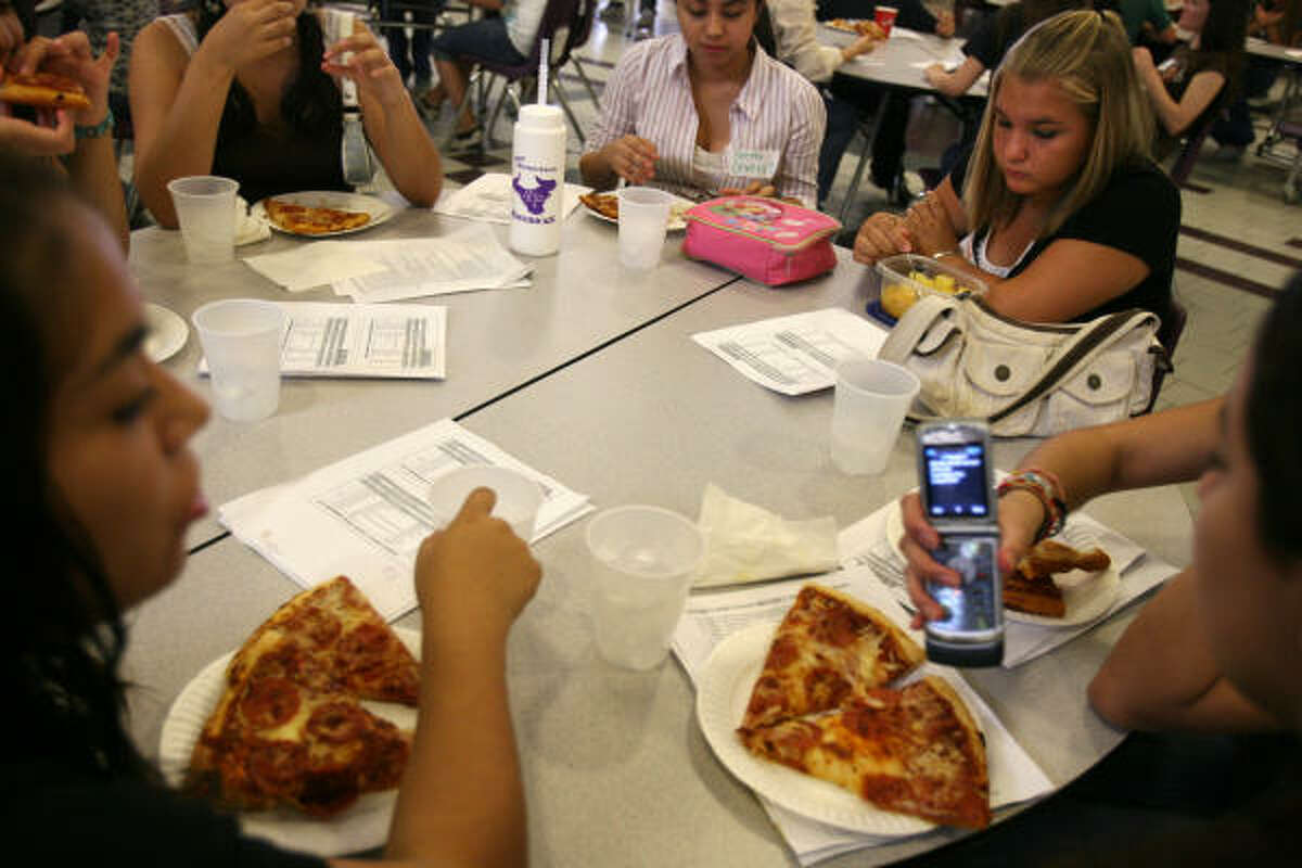 Isabel Hernandez eats a fruit bowl she packed for lunch while her friends munch on pizza during freshman orientation at Morton Ranch High School in Katy.