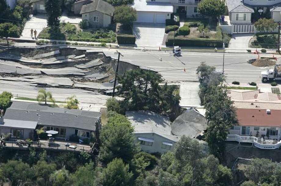 Nine homes in San Diego had severe structural damage from Wednesday's landslide, which cut a 50-yard-long chasm in the street. Photo: CHRIS PARK, ASSOCIATED PRESS