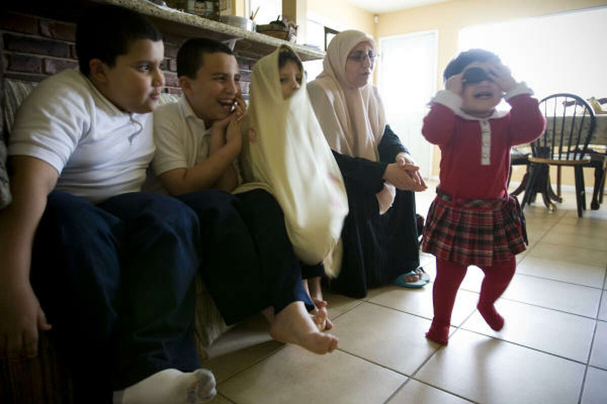 Mounira Belhacel-Bouchikhi watches as her children, from left, El-Faroq Bouchikhi, 9, Ilies, 12, Bushra, 7 and Shareefah, 18 months, have some fun during an interview about her husband Sheikh Zoubir Bouchikhi. She visits her husband weekly at a detention center where he leads prayers.