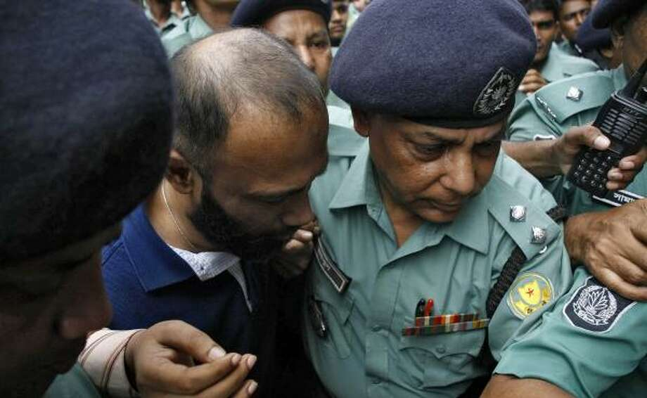 Police escort Arafat Rahman, younger son of former Bangladeshi Prime Minister Khaleda Zia, to court in September on corruption charges. He and his mother are accused of illegally influencing a government contract. Photo: STRDEL, STRDEL/AFP/GETTY IMAGES