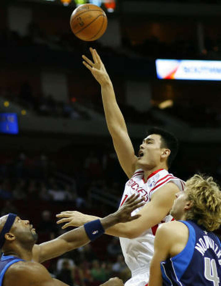 Rockets center Yao Ming goes up strong against against Eric Dampier, left, and Dirk Nowitzki in a loss to the Mavericks on Saturday. The Rockets are the only team in the NBA with just two players scoring in double figures. Photo: Steve Ueckert, Houston Chronicle