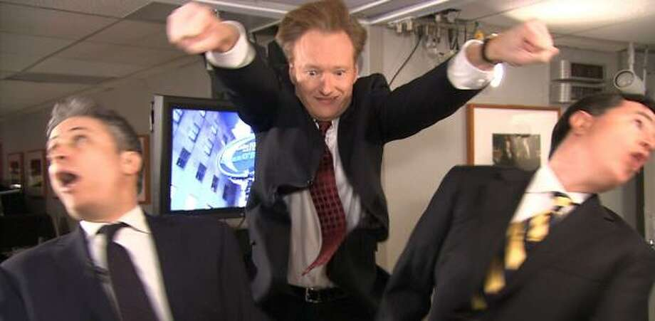 Conan O'Brien, center, mock-punches Jon Stewart, left, and Stephen Colbert on Late Night With Conan O'Brien. Photo: NBC