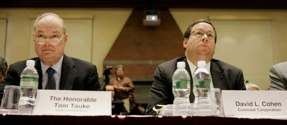 Tom Tauke, Verizon executive vice president, and David Cohen, executive vice president of Comcast Corp., listen to testimony at the FCC's hearing in Cambridge, Mass., on Monday. Photo: STEPHAN SAVOIA, ASSOCIATED PRESS