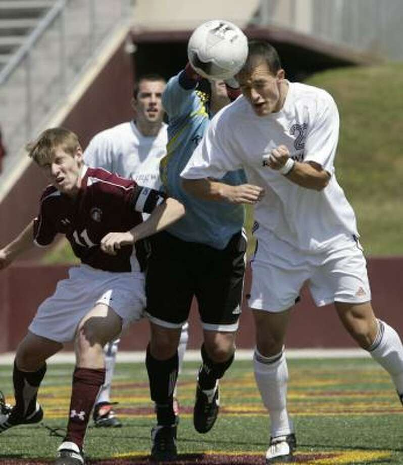 Kingwood goalkeeper Sean Fox, center, and teammate Blake Shannon, right, try to keep the ball away from Cinco Ranch's Preston Davis in the first half of their Region III-5A final. Photo: JULIO CORTEZ, CHRONICLE
