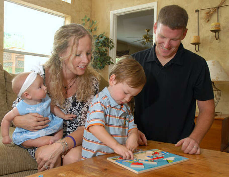 Erin Scott, second from left, was recently diagnosed with colon cancer. A York Junior High counselor, Scott has vowed to beat the disease and be back in school next year. Here, she is helping her 2-year-old son Leighton assemble a puzzle with her 5-month-old daughter Leighton and husband Matt. Photo: David Hopper, For The Chronicle