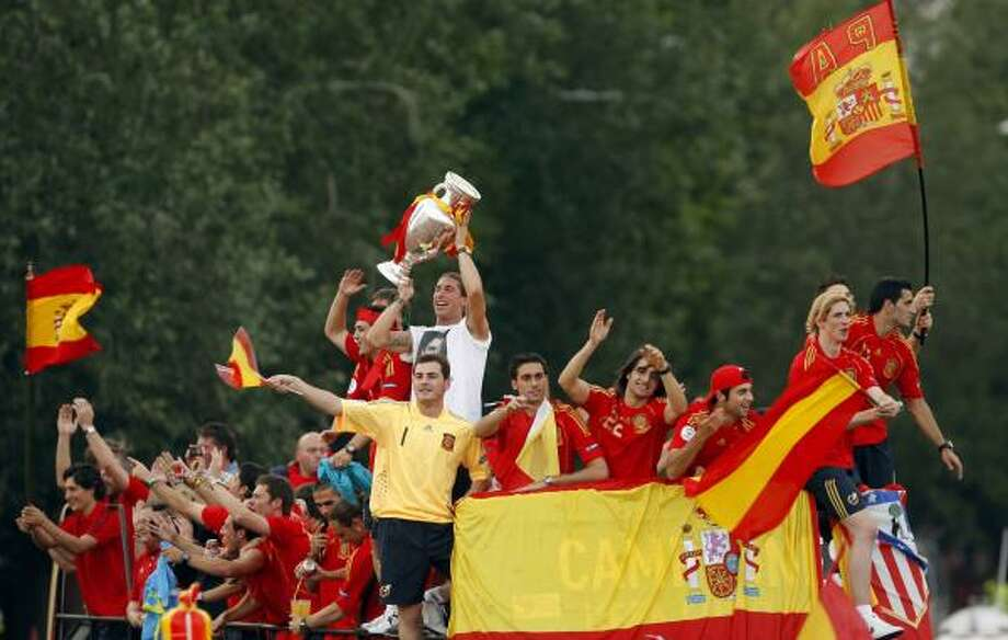 Spain players, fresh off their 1-0 victory over Germany to win the 2008 European Championship, celebrate with fans upon their arrival in Madrid on Monday. Photo: DANIEL OCHOA DE OLZA, ASSOCIATED PRESS