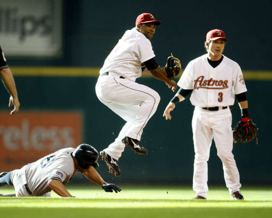 FIRST INNING: Astros shrotstop Miguel Tejada leaps over the Yankees' Johnny Damon at second while turning a double play in the early going. Photo: Karen Warren, Chronicle