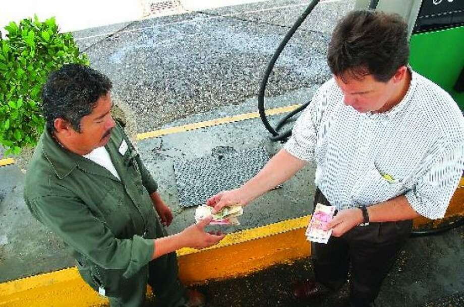 Manuel Arechiga, right, pays Juan Manuel Pulido Carreon, an attendant at a Pemex station in Nuevo Laredo, $70 for a tank of diesel that would have cost him $145 at his own station. Photo: ULYSSES S. ROMERO, FOR THE SAN ANTONIO EXPRESS-NEWS