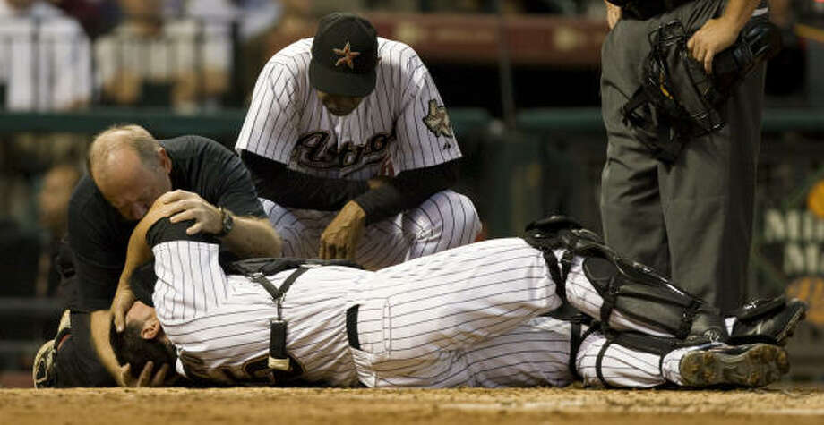 Astros' trainer Dave Labossiere and Astros' manager Cecil Cooper tend to Houston Astros catcher Humberto Quintero as he lay on the ground after being injured during the second inning against the Los Angeles Dodgers at Minute Maid Park on Tuesday. Photo: Brett Coomer, Chronicle