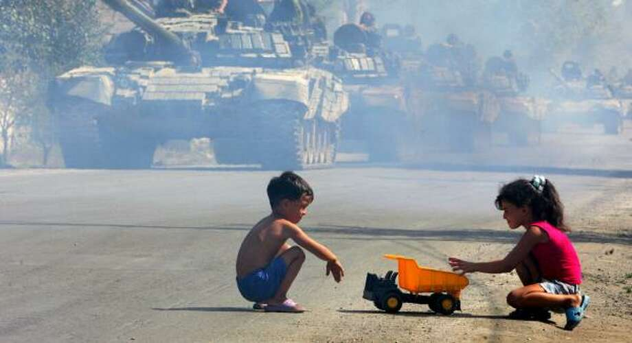 Russian tanks move through as children play in the street Saturday in Tskhinvali, South Ossetia. Photo: VIKTOR DRACHEV, AFP/GETTY IMAGES