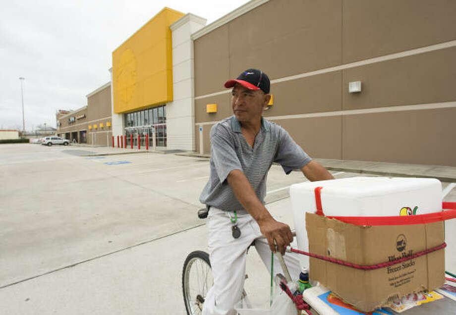Vendor Jose Rodriguez rides by a closed Circuit City store in the Sharpstown Plaza shopping center. The proprietors of the smaller stores in the strip center say business has slowed since the main tenant left. Photo: BRETT COOMER, Chronicle