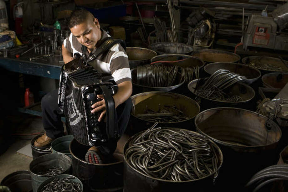 Jorge Vazquez finds time to practice his accordion in the workshop of his family's business, Bravo U-Bolts & Fasteners, in Houston. Photo: Brett Coomer, Chronicle