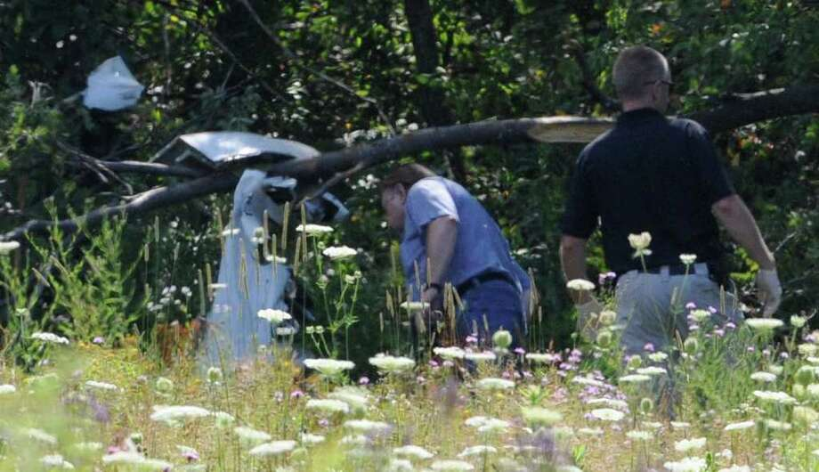 Investigators from the Albany County Sheriff's department and the NTSB look over the wreckage at the scene of a plane crash near Elm Road in East Berne, N.Y. July 26, 2011,  that took the life of one man.  (Skip Dickstein / Times Union) Photo: SKIP DICKSTEIN / 2011