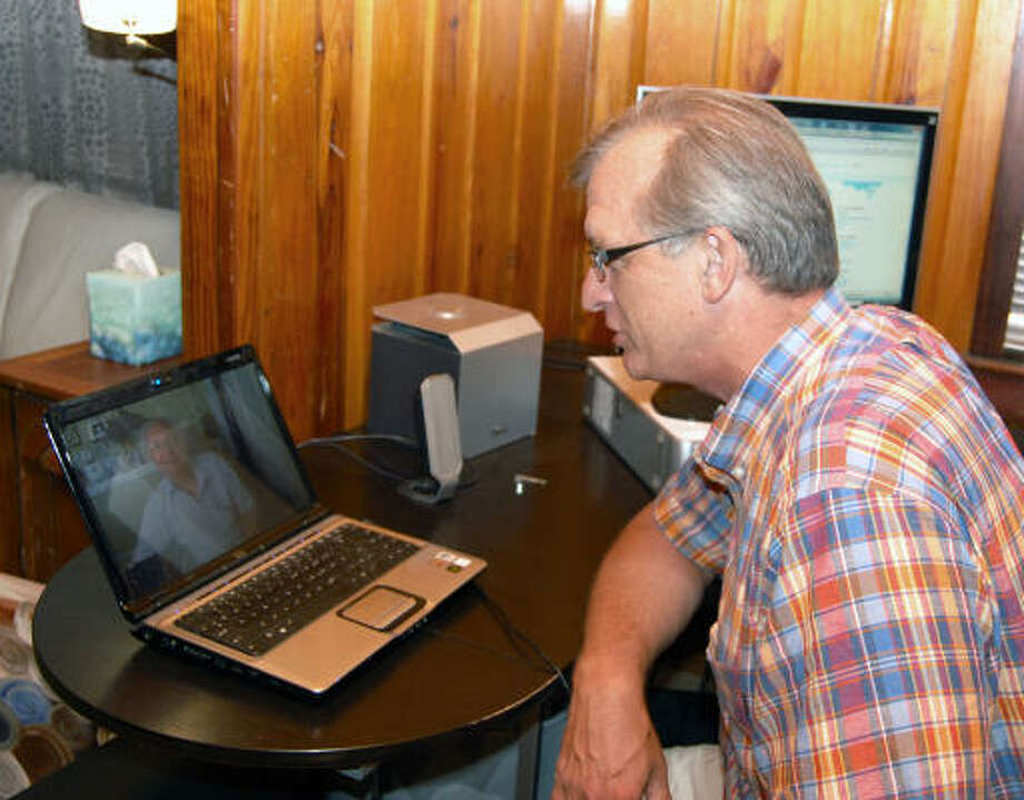 FROM THE OFFICE: Tim Gusey demonstrates how he uses Skype to counsel people overseas. Photo: Wendy Rudnicki, For The Chronicle