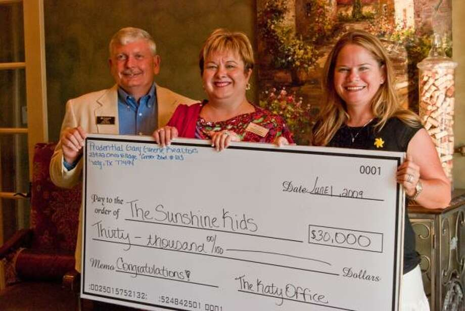 SPREADING A LITTLE 'SUNSHINE': The Katy office of Prudential Gary Greene, Realtors' Bob Miles, left, and Christi Borden, center, present a check for $30,000 raised at the annual Katy Sunshine Fest to Shannon Lillis, director of operations for The Sunshine Kids Foundation, which provides group activities and emotional support for children with cancer.