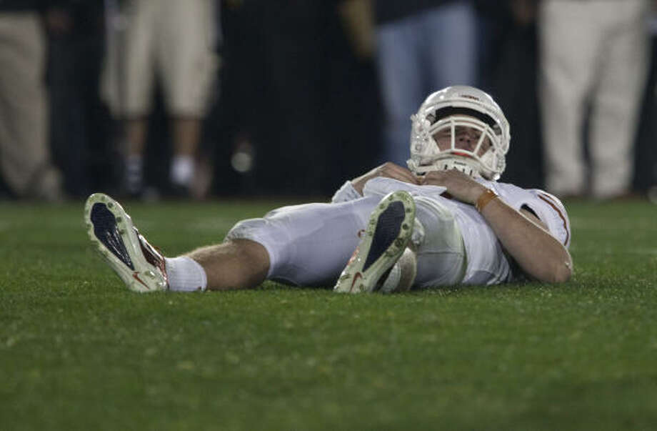 Texas quarterback Garrett Gilbert looks up from the turf after throwing an interception during the fourth quarter. Photo: Smiley N. Pool, Chronicle
