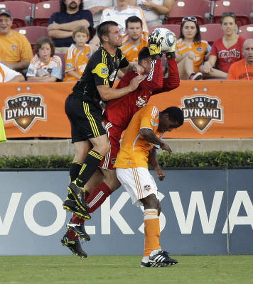 Dynamo goalkeeper Pat Onstad pulls in a save between Dynamo midfielder Lovel Palmer and Crew forward Jason Garey. Photo: Bob Levey, Getty Images