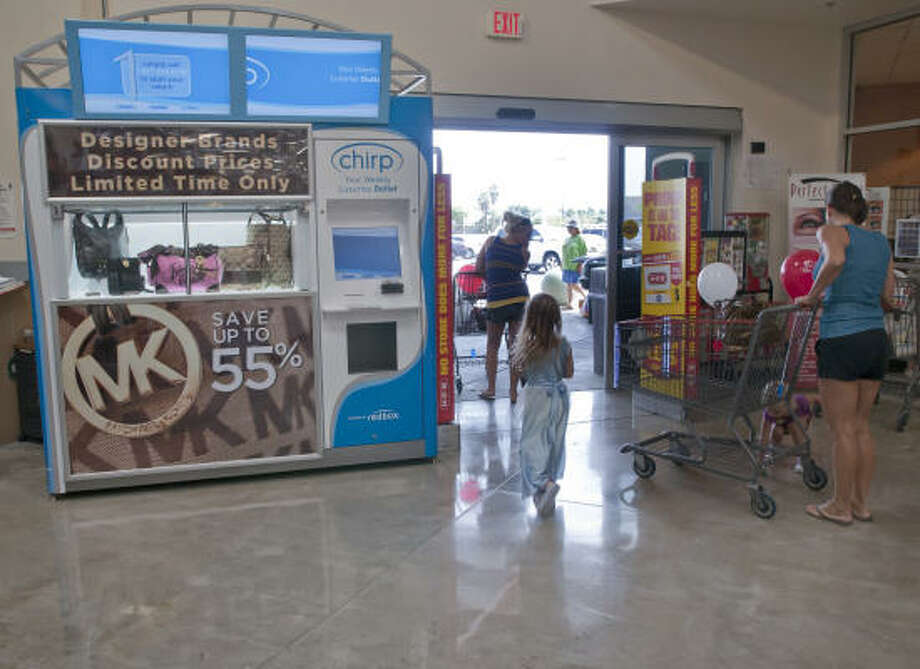 H-E-B shoppers pass by a Chirp kiosk, a high-tech vending machine, as they leave the store on Blackhawk. Photo: Kim Christensen :, For The Chronicle