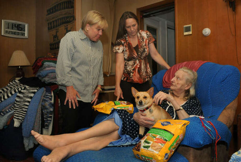 JERRY BAKER: FOR THE CHRONICLE IN-HOME VISIT: Meals-on-Wheels volunteers Kris Dimlich, left, and Renee Blacklaws visit with client Jenny Harris and her dog, Gracie, at Harris' home in The Woodlands. Photo: Jerry Baker, For The Chronicle