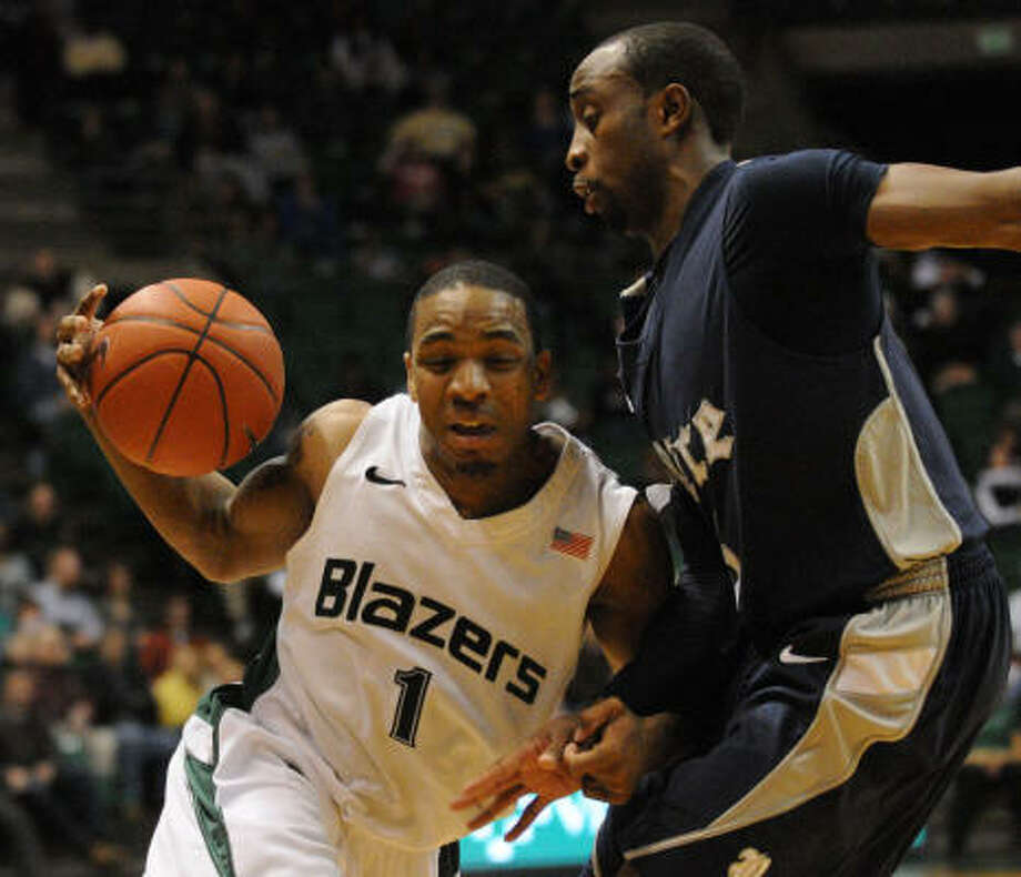 Rice's Tamir Jackson, right, defends UAB's Aaron Johnson (1) in the first half on Saturday night. Photo: Hal Yeager, AP