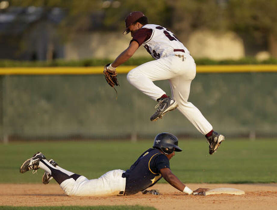 Cy Ranch's Leon Byrd (1) reaches back to second base after Cy Fair's Avain Rachel tries to catch the ball. Photo: Karen Warren, Chronicle