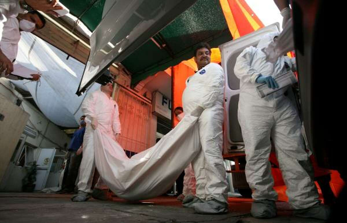 Morgue workers move a from a refrigerated truck at the entrance of a funeral home in Mexico City. The body came from the pits near San Fernando.