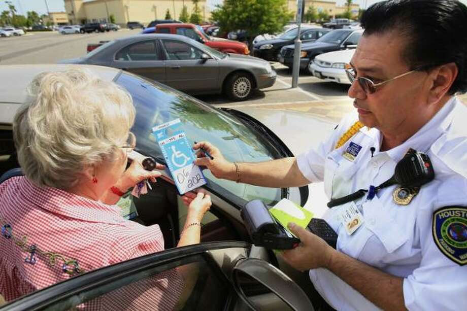 Parking Enforcement Supervisor Roland De La Cerda explains to a woman the importance of hanging her handicap tag from her mirror, which she forgot to do Wednesday. Photo: Cody Duty, Chronicle