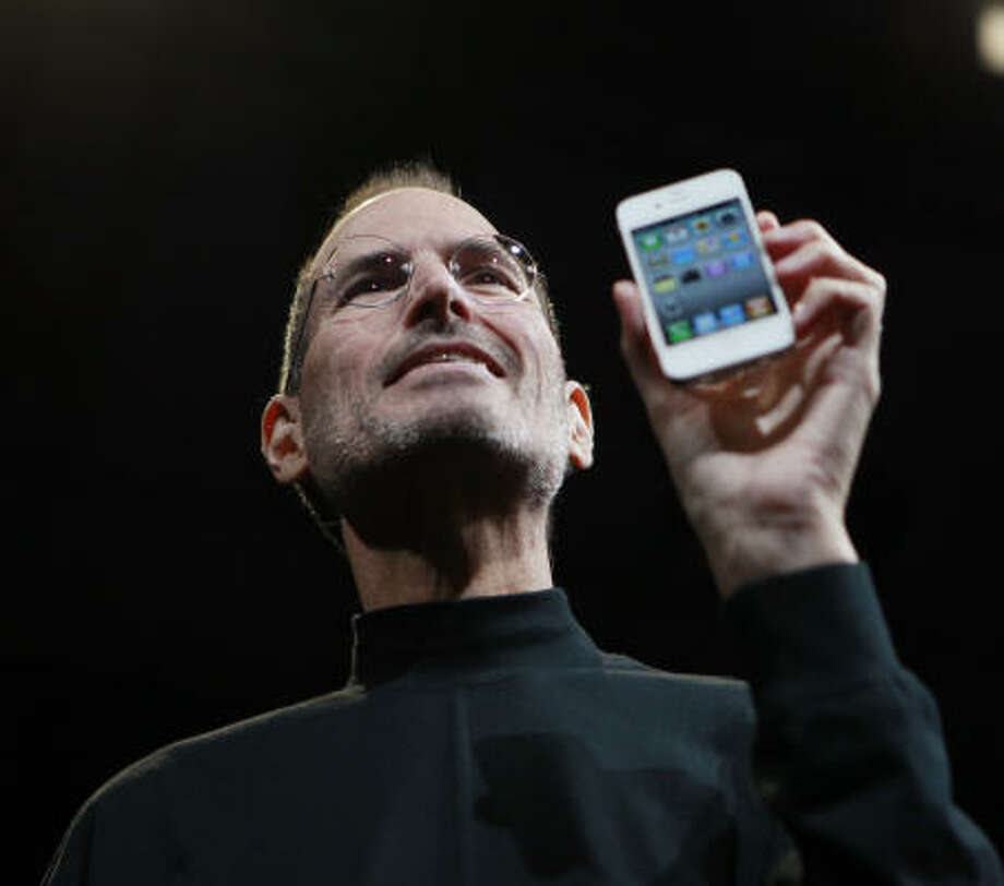 Apple CEO Steve Jobs holds the new iPhone 4 at an Apple conference Monday in San Francisco. Photo: Paul Sakuma:, AP